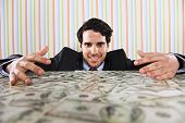 stock photo of greed  - Businessman at his office with lots of money - JPG