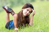 Beautiful young Filipina woman enjoying nature lying on her stomach facing the camera in a green grassy field with a thoughtful expression