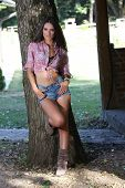 Young Woman Leaning On Tree
