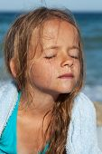 Little girl soaking up the sun on the windy sea shore - closeup portrait