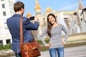 Tourists taking picture on travel in Barcelona. Happy urban young couple taking photo portrait with