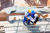stock photo of scaffold  - Construction site Team or architect and builder or worker with helmets discuss on a scaffold construction plan or blueprint or checklist - JPG