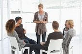 Rehab group listening to woman standing up introducing herself at therapy session