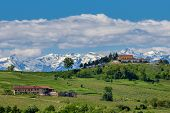 Rural houses on green fields and mountains with snowy peaks on background in spring in Piedmont, Nor