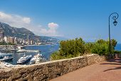Sidewalk with ornate lamppost and view over port Hercules and buildings of Monte Carlo, Monaco.