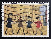 A stamp printed in Great Britain shows Children Playing by L.S. Lowry