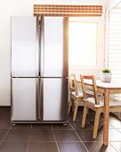 Luxury steel refrigerator on the kitchen, bright sun light from the windows, beautiful apartment int