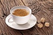stock photo of coffee grounds  - Cup of cappuccino with ground cinnamon and sugar cubes on the plate - JPG