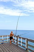 man at Old Wooden Fishing Pier In The Outer Banks
