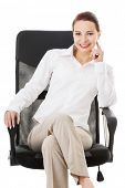 Beautiful business woman, boss sitting on a chair. Isolated on white.