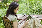 Young Woman With Tablet PC In A Garden