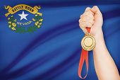 Medal In Hand With Flag On Background - State Of Nevada. Part Of A Series.