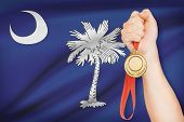pic of south american flag  - Sportsman holding gold medal with State of South Carolina flag on background - JPG