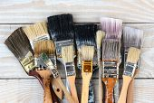 High angle shot of a group of old used paint brushes on a rustic wooden table. Horizontal format.