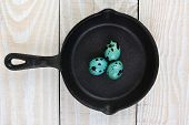 High angle shot of a cast iron frying pan  with three blue speckled eggs. Horizontal format on a rus