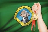 Medal In Hand With Flag On Background - State Of Washington. Part Of A Series.
