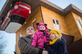 pic of inverted  - Family of three against the inverted house with red car - JPG