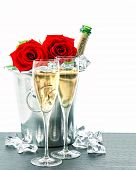 Two Glasses, Bottle Of Champagne And Red Roses