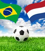 Soccer Ball On Grass And Flags Of Brazil And Netherlands