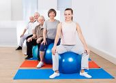 People Sitting On Fitness Balls In Exercise Class