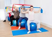 People With Resistance Bands Sitting On Fitness Balls
