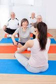 picture of senior class  - Rear view of female trainer training senior customers on floor in yoga class - JPG