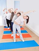 Trainer And Senior Customers Doing Stretching Exercise