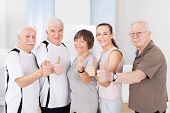 Confident People Showing Thumbs Up At Healthclub