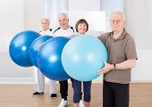 Confident Senior People Carrying Fitness Balls