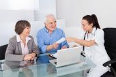 Doctor Giving Prescription To Senior Couple In Clinic