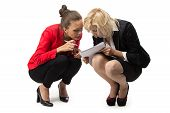 Two businesswoman sitting with sheet of paper