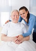 Caretaker With Senior Man At Nursing Home