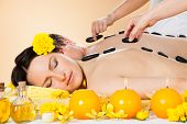 Couple Receiving Hot Stone Therapy At Spa