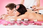 Couple Receiving Massage With Herbal Compress Stamps At Spa