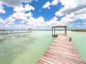Idyllic pier and palapa hut in Bacalar lagoon in Mexico