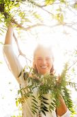 Portrait Of Smiling Young Woman In Foliage