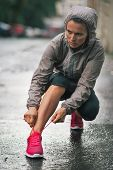 Fitness Young Woman Tying Shoelaces Outdoors In Rainy City