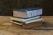 Vintage Old Books On Wooden Deck Table With Soil Wall
