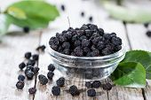 stock photo of chokeberry  - Ddried Chokeberries in a small bowl  - JPG