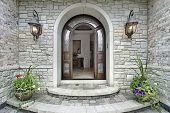 image of entryway  - Arched stone entry of luxury suburban home - JPG