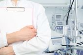 Doctor In White Coat With A Clipboard On A Background Of A Hospital Ward.