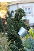 stock photo of garden sculpture  - Botanical garden sculpture of a man with a bucket - JPG