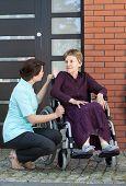 Nurse Talking With Senior Woman On Wheelchair