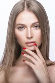Beautiful young girl with a light natural make-up and red nails.