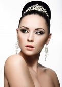 Beautiful dark-haired girl in the image of a bride with a tiara in her hair. Beauty face.