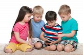 Kids With A Gadget On The Carpet