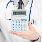 Doctor Holdling In His Hand Calculator - Heath Care Concept