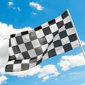 Checkered Flag Waving In The Wind With White Clouds On Background - Outdoors Shoot