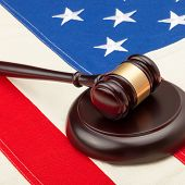 Wooden Judge Gavel And Soundboard Laying Over Usa Flag - Closeup Shot