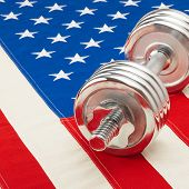 Metal Dumbbell Over Us Flag As Symbol Of Healthy Life Style - Studio Shot